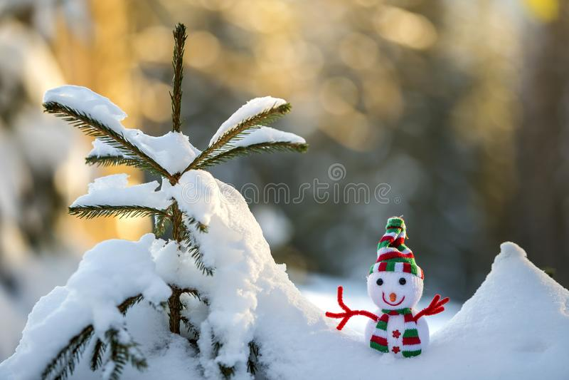 Petit bonhomme de neige drôle de bébé de jouet dans le chapeau et l'écharpe tricotés dans la neige profonde dehors sur le fond bl photos libres de droits