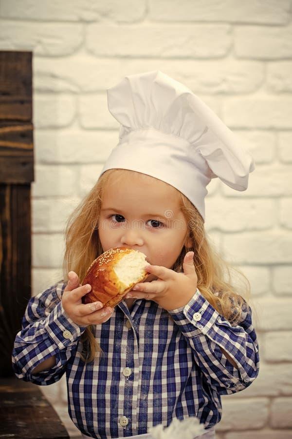 Petit boulanger Enfant mangeant le petit pain de pain sur le mur de briques blanc photo libre de droits