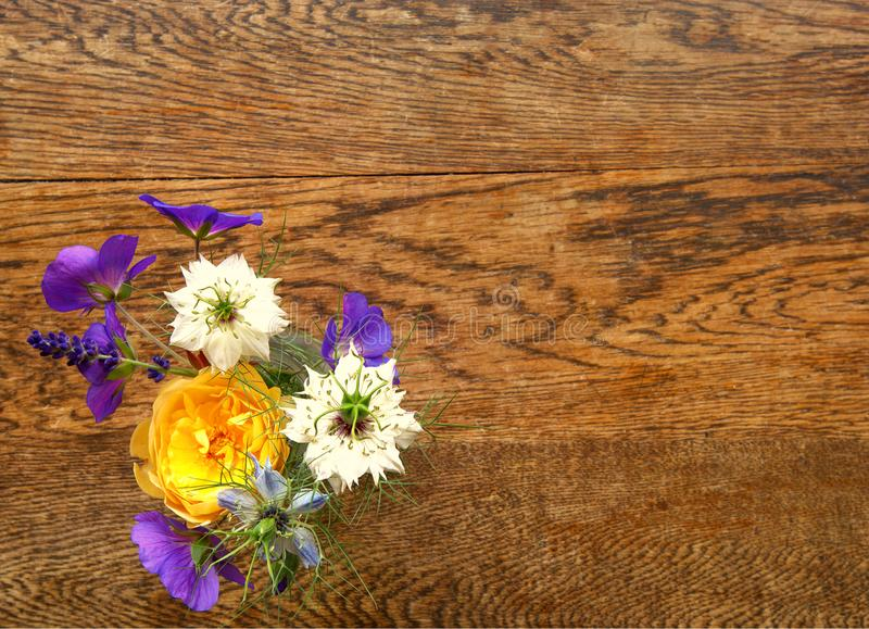 Petit petit bouquet coloré des fleurs sur une table en bois photographie stock libre de droits