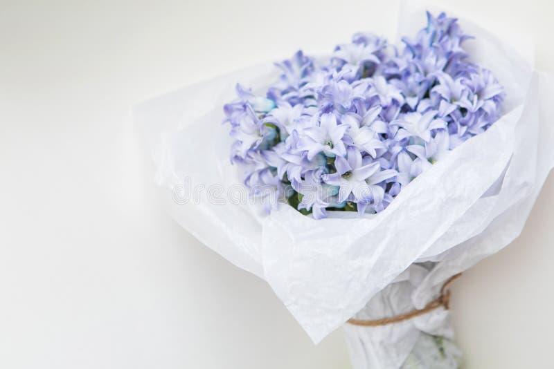 Petit bouquet des jacinthes bleues de fleurs de ressort enveloppées en livre blanc sur un fond blanc images stock
