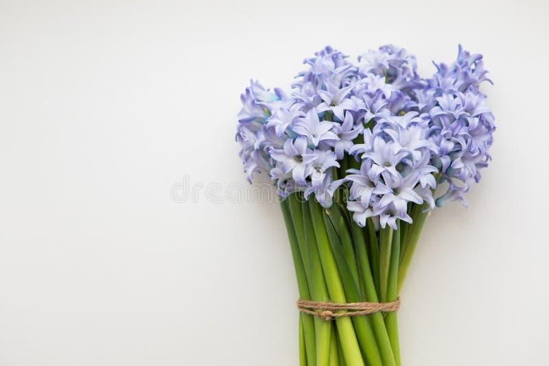 Petit bouquet des jacinthes bleues de fleurs de ressort enveloppées en livre blanc sur un fond blanc photographie stock