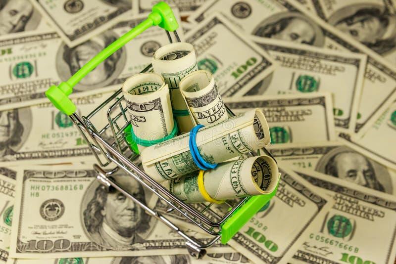 Petit caddie avec des rouleaux de dollars sur le fond d'U S Cents billets d'un dollar Concept consumant photographie stock