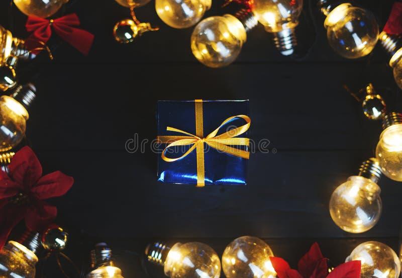 Petit cadeau bleu à l'intérieur des ampoules et poinsettia rouge sur W noir photos libres de droits