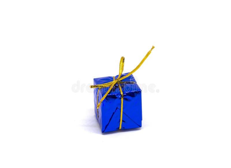 Petit cadeau bleu sur le fond blanc Boîte-cadeau de Noël dans le feuillage s'enveloppant avec l'arc de fil d'or photographie stock libre de droits