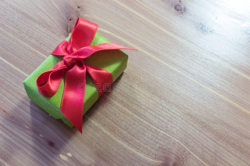 Petit cadeau, diagonal sur une table en bois, enveloppée en vert avec le grand arc rouge de satin photos libres de droits