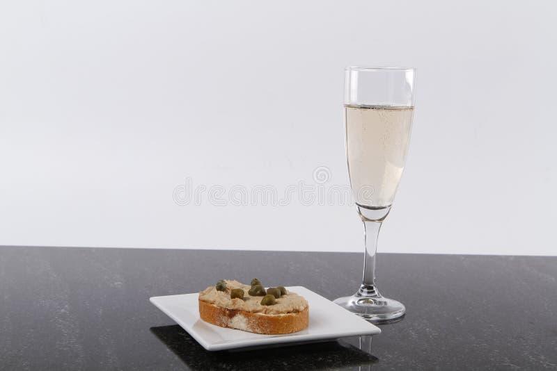 Petit canape avec le thon et les câpres et un verre de champagne image libre de droits