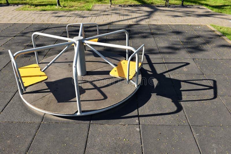 Petit carrousel sur une image vide de terrain de jeu au printemps - photos stock