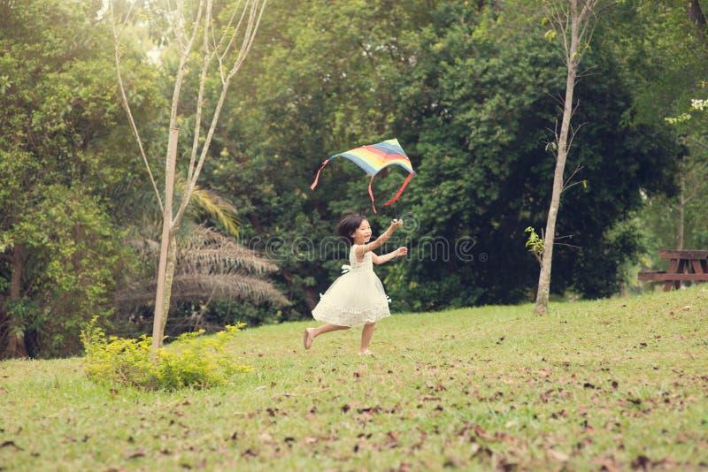 Petit cerf-volant asiatique heureux de vol de fille au parc photographie stock libre de droits