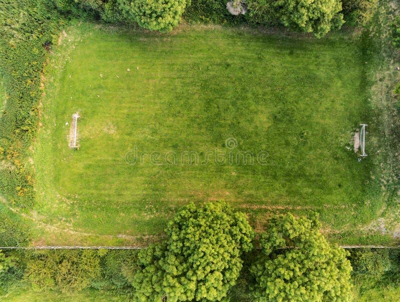 Petit champ d'herbe du football de pays entouré par des arbres, vue aérienne image libre de droits