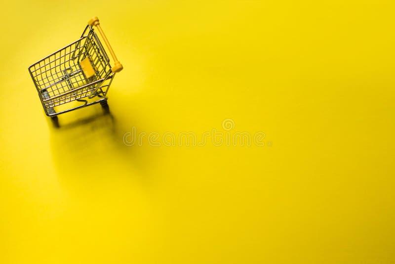 Petit chariot à un arrière-plan jaune Concept de Black Friday et de Cybermonday photos libres de droits