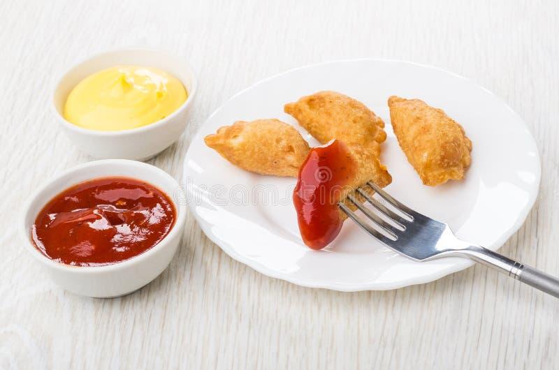 Petit cheburek avec le ketchup ficelé sur la fourchette dans le plat, sauces images libres de droits