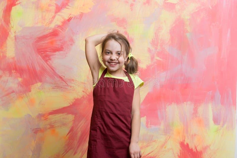 Petit chef de fille avec le visage heureux dans le tablier de cuisinier photos libres de droits