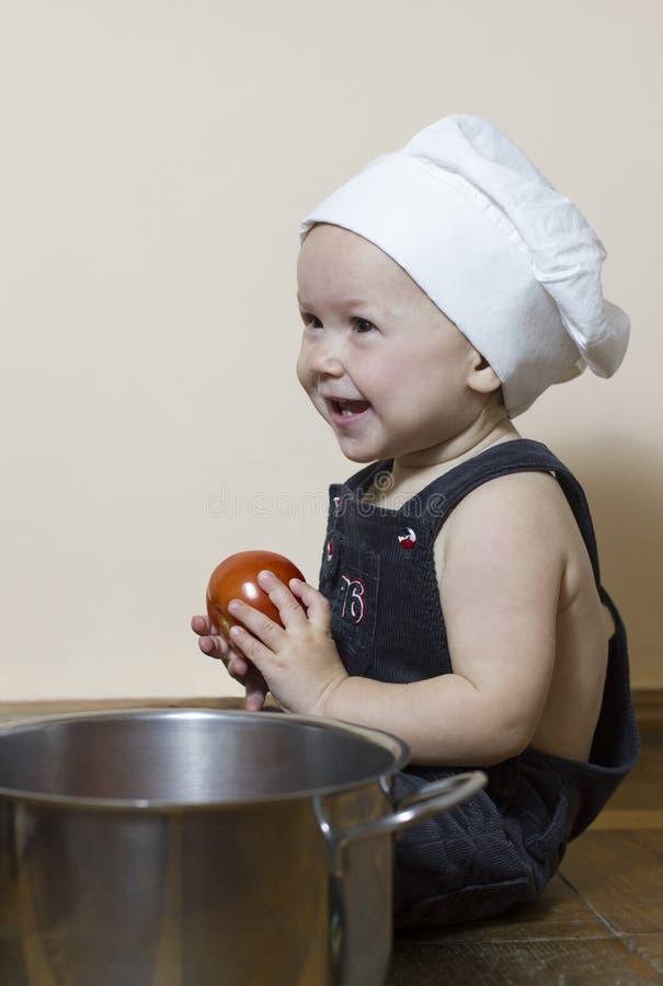 Petit chef heureux de garçon avec la tomate rouge photos stock