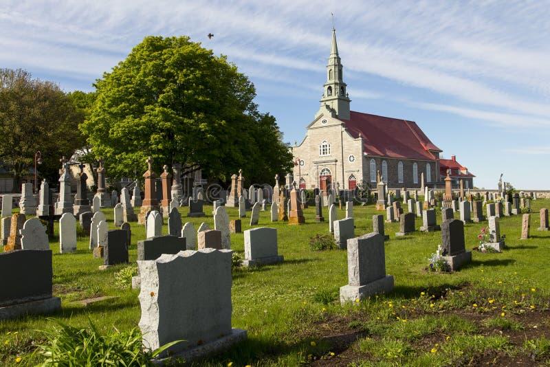 Petit cimetière de village et 1737 néoclassiques patrimoniaux église catholique en pierre en Saint-Jean, île d'Orléans image stock