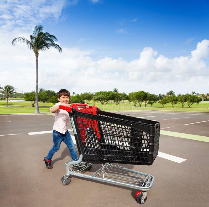 Petit client mignon avec le chariot vide au parking image libre de droits