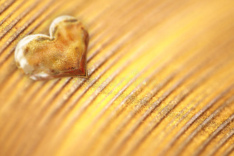 Petit coeur d'or brillant sur la poudre d'or image stock