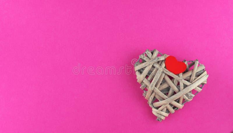 Petit coeur en bois rouge étendu sur un grand coeur léger de rotin image stock