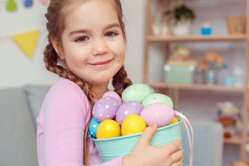 Petit concept mignon de célébration de Pâques de fille à la maison tenant le seau avec des oeufs image stock