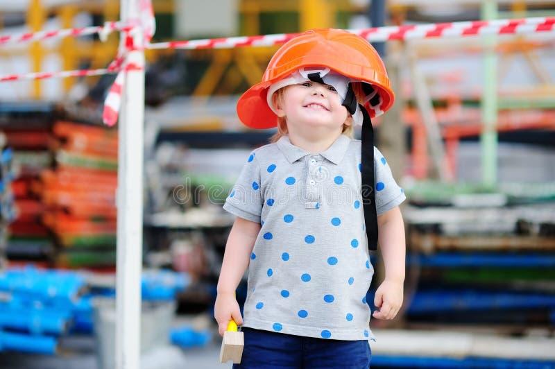Petit constructeur drôle dans des masques avec le marteau fonctionnant dehors photo libre de droits