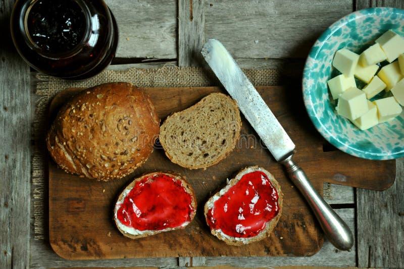Petit déjeuner à la maison avec la confiture, le beurre et le pain de myrtille images stock