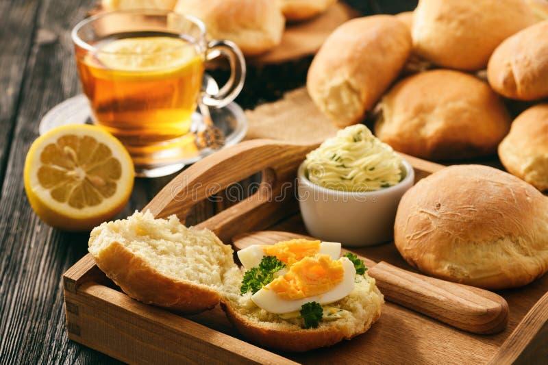 Petit déjeuner à la maison - rouleaux de pain fait maison, tasse de thé, oeufs à la coque et beurre persillé d'ail image stock