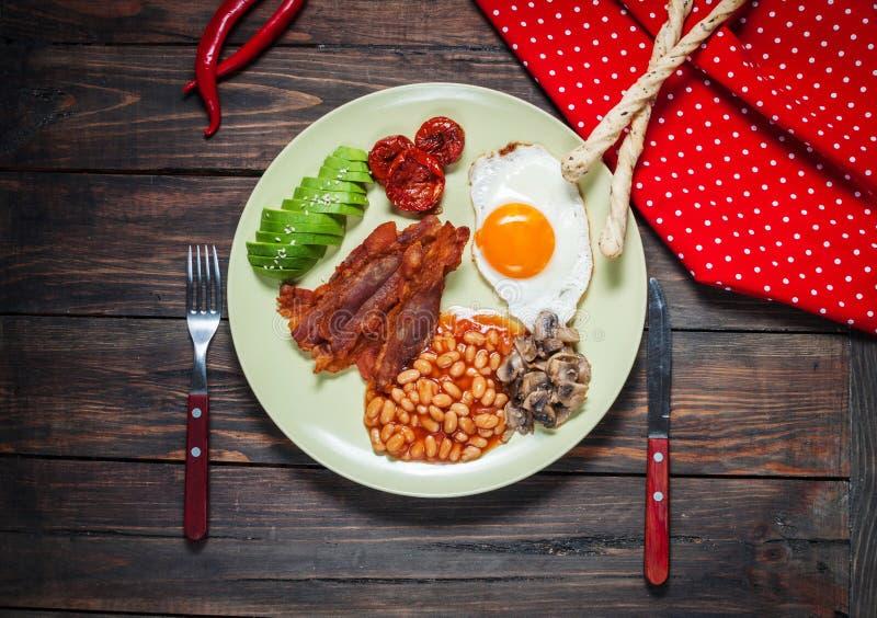 Petit déjeuner anglais de lard, oeuf au plat, haricots, champignons, avocat photo stock