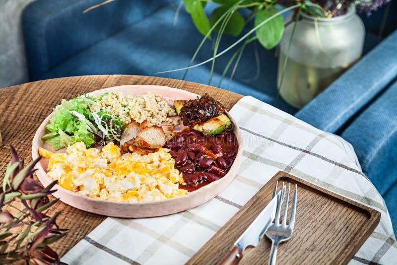 Petit déjeuner anglais moderne de petit déjeuner continental plein avec les oeufs brouillés, le bulgur, les haricots, l'avocat et image stock