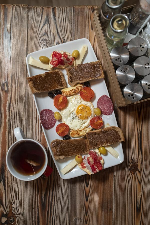 Petit déjeuner avec l'oeuf au plat, le pain de seigle, la grenade, la pâte de caroube, les fromages, les olives, le salami sec, l images libres de droits