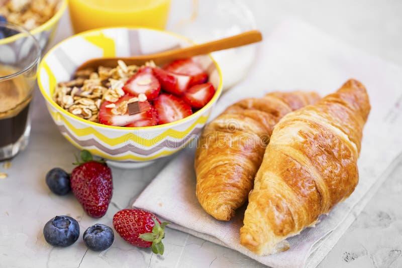 Petit déjeuner avec la cuvette et les croissants de muesli photographie stock
