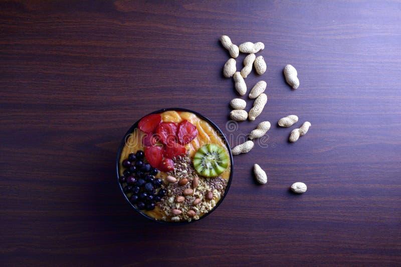 Petit déjeuner avec le muesli, smoothie de myrtille d'acai et kiwi, fruits sur le fond vert Concept sain de nourriture La configu image libre de droits
