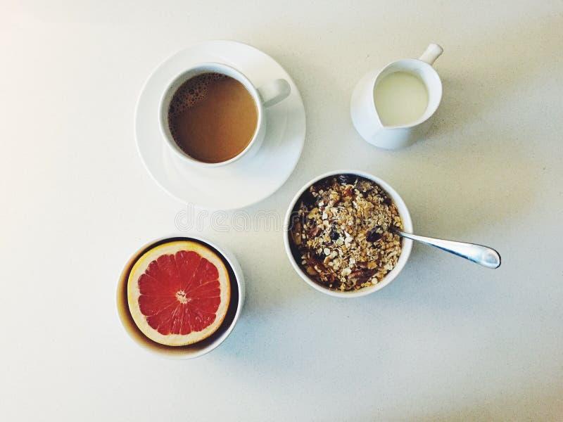 Petit déjeuner : Café, lait, cuvette de muesli et pamplemousse rose demi image stock