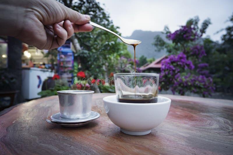 Petit déjeuner chaud de matin de tasse de café blanc sur la table en bois avec le fond brouillé de montagne Foyer sélectif, petit image libre de droits