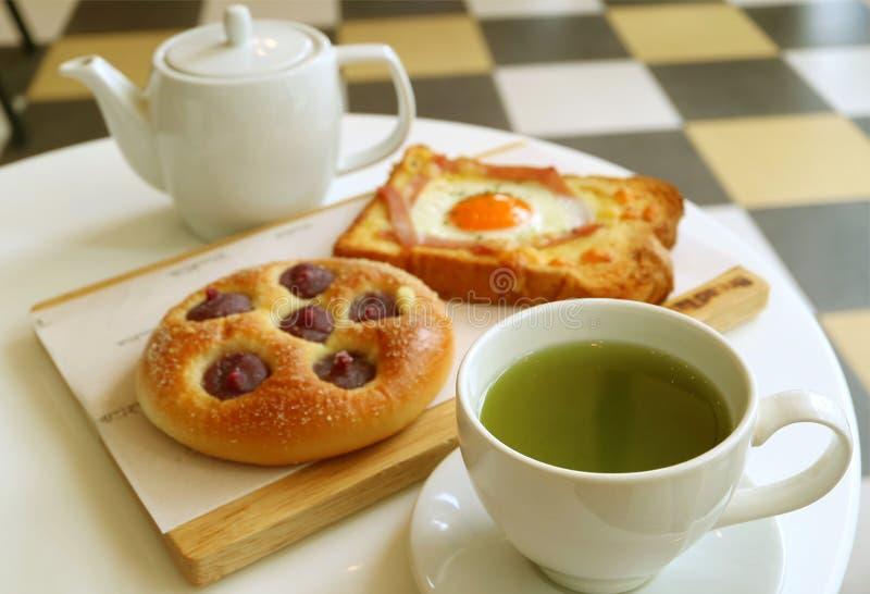 Petit déjeuner délicieux de thé vert chaud avec du pain grillé et le petit pain cuits au four photos stock