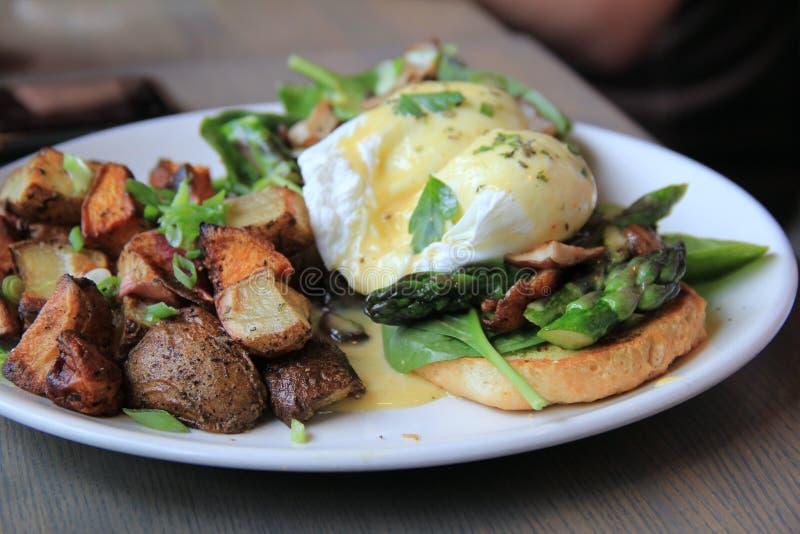 Petit déjeuner délicieux des oeufs pochés et des fritures de maison photo stock