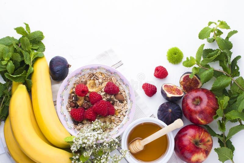 Petit déjeuner délicieux et sain sur un fond blanc Gruau de farine d'avoine, framboise, miel, bananes, figues, frais en bon état, image libre de droits