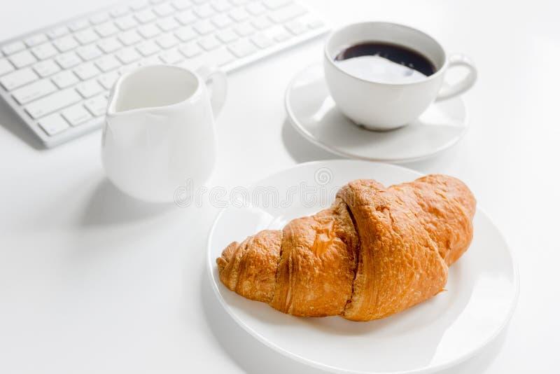 Petit déjeuner d'affaires dans le bureau avec le clavier, le café et le croissant sur le fond blanc de table photographie stock libre de droits