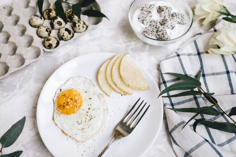 Petit déjeuner d'oeuf au plat et de poire d'un plat blanc avec une fourchette Dans un bol en verre, le yaourt et un fruit du drag images stock