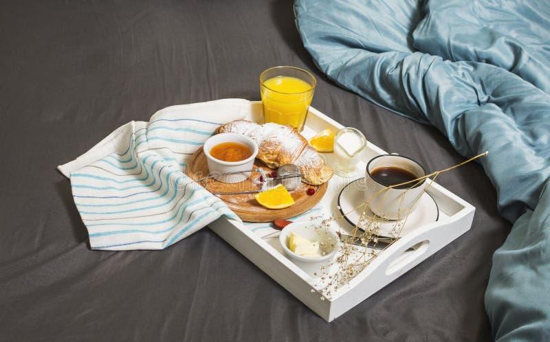 Petit déjeuner dans le lit avec du café, les croissants et le jus d'orange photographie stock