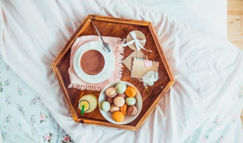 Petit déjeuner dans le lit avec la carte vierge vide Tasse de café, de jus, de macarons, de fleur et de giftbox sur le plateau en photo libre de droits