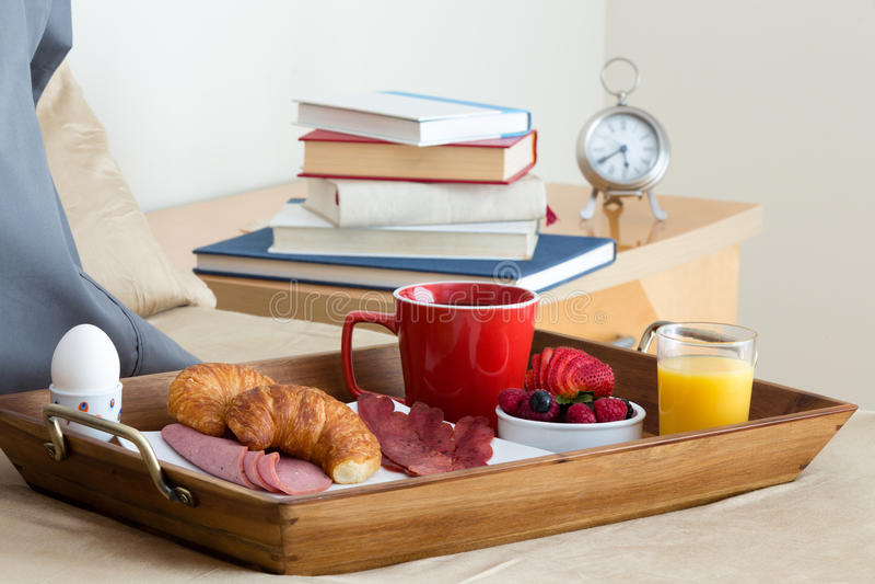 Petit déjeuner dans le plateau de lit sur le lit à côté de la table de chevet image stock