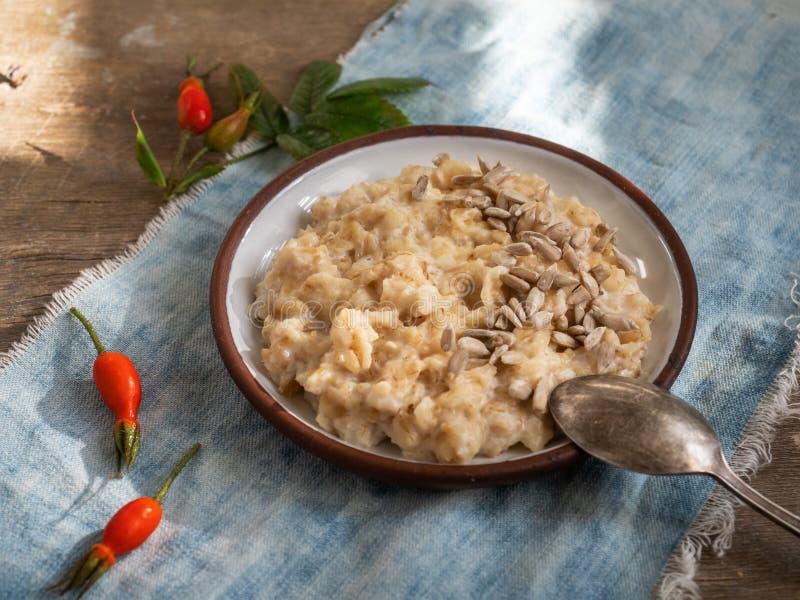 Petit déjeuner de farine d'avoine sur le lait dans un plat rond avec une cuillère, servant sur des baies d'une serviette de denim photos stock