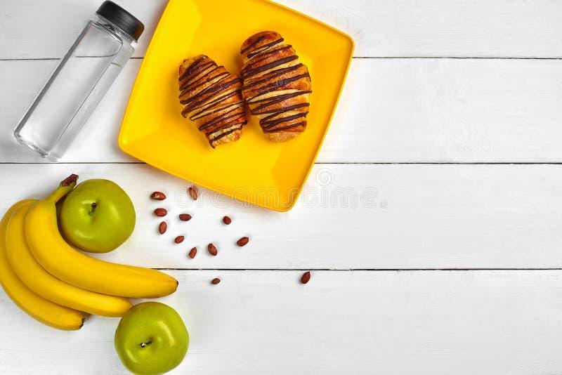Petit déjeuner de fruit avec l'espace libre sur la table en bois Croissant, banane, pomme, écrous et une bouteille de l'eau Vue s image libre de droits