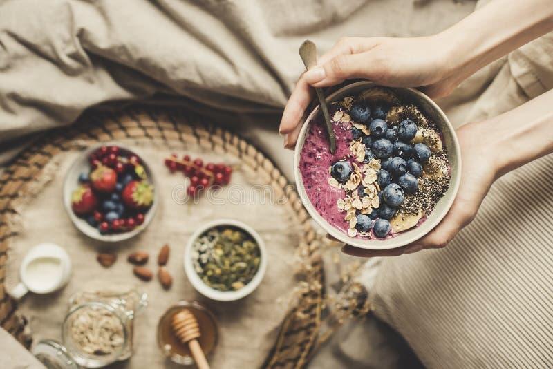 Petit déjeuner de Helthy dans le lit Les mains tenant le smoothie délicieux roulent avec les myrtilles, l'avoine roulée et les gr photos stock