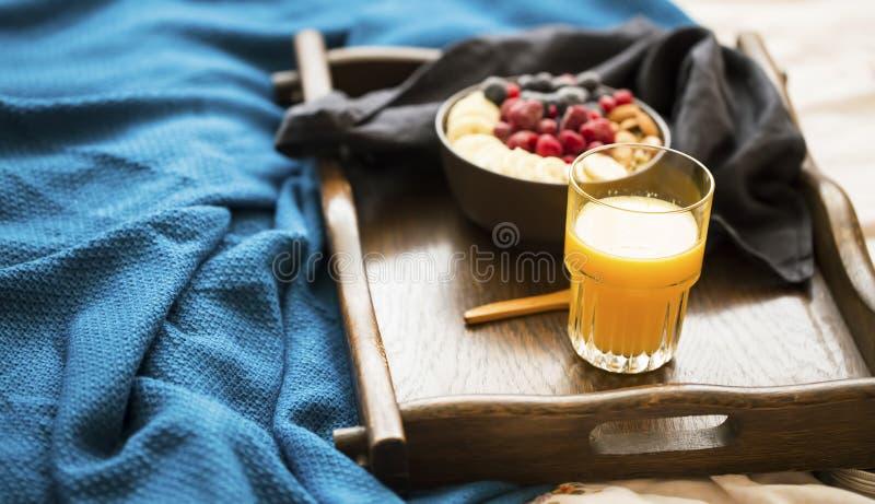 Petit déjeuner de lit avec le verre du jus d'orange et d'un bol de farine d'avoine avec les baies, la banane et les amandes fraîc images stock