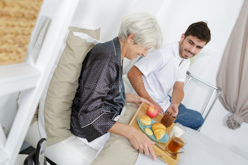 Petit déjeuner de portion d'infirmière à la femme supérieure à la maison images stock