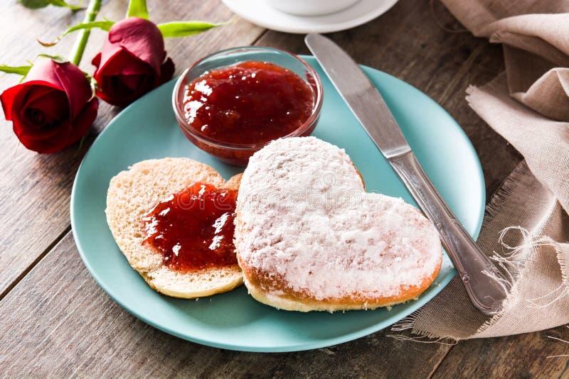 Petit déjeuner de Saint-Valentin avec du café, le petit pain en forme de coeur et la confiture de baie image libre de droits
