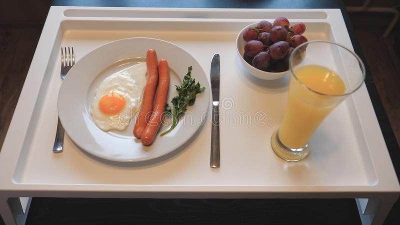 Petit déjeuner de Tableau des oeufs brouillés avec des saucisses, jus, fruit photographie stock