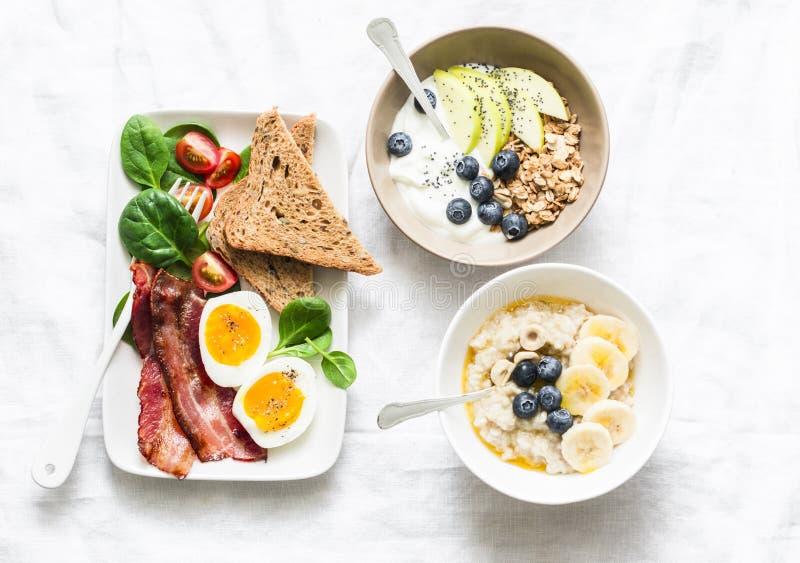 Petit déjeuner doux et savoureux varié - lard avec l'oeuf et les légumes, la salade d'épinards, la granola de yaourt et le fruit, photo libre de droits