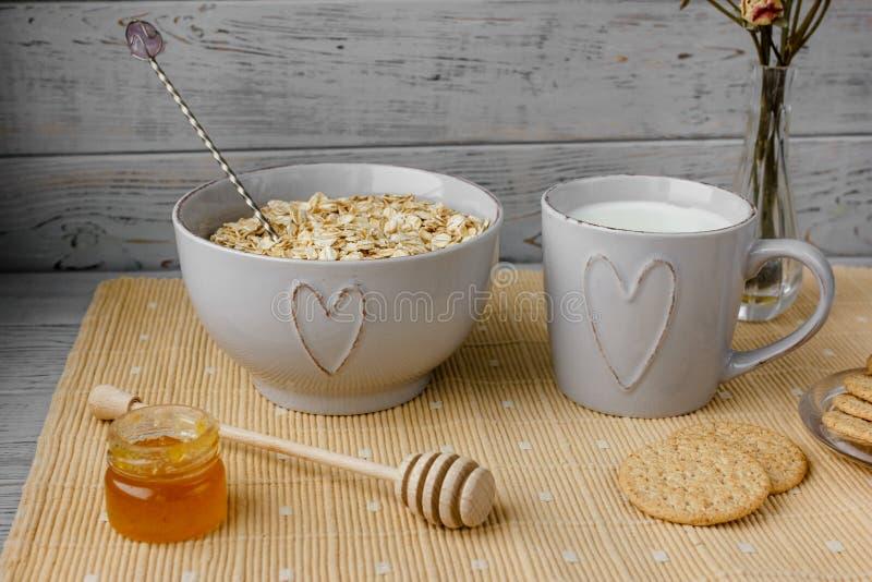 Petit déjeuner entier sain : farine d'avoine, lait, biscuits, miel et vase avec des roses photo stock