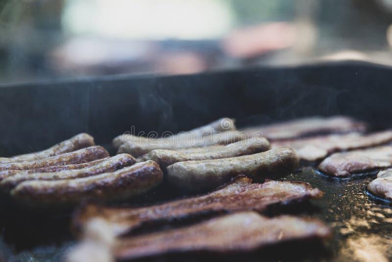 Petit déjeuner faisant cuire sur un gril de camp dehors images stock
